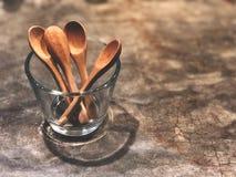 Houten lepels in glas op de cementvloer met koffielicht stock afbeeldingen