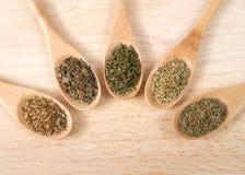 Houten lepels met gemeenschappelijke Italiaanse kruiden op houten lijst Royalty-vrije Stock Foto
