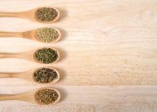Houten lepels met gemeenschappelijke Italiaanse kruiden op houten lijst met exemplaarruimte Royalty-vrije Stock Foto