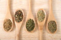 Houten lepels met Italiaanse kruiden op houten lijst Stock Foto's