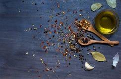 Houten lepels met specerij en knoflook en olijfolie stock fotografie