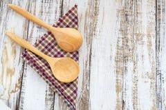 Houten lepels op geruite doek die op houten oppervlakte liggen Royalty-vrije Stock Foto