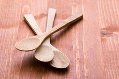 Houten lepels op houten lijst Stock Afbeelding