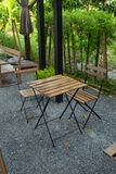 Houten lijst en stoelen die in de tuin zetten Stock Foto's