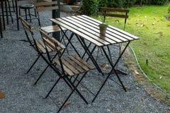 Houten lijst en stoelen die in de tuin zetten Royalty-vrije Stock Afbeelding