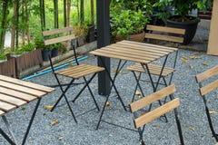 Houten lijst en stoelen die in de tuin zetten Stock Afbeelding