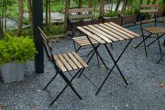 Houten lijst en stoelen die in de tuin zetten Stock Afbeeldingen