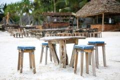 Houten lijst en stoelen op het strand Meubilair voor het lounging Stock Afbeeldingen