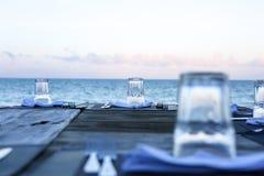 Houten lijst en stoelen op het strand Meubilair voor het lounging Stock Afbeelding