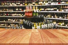Houten lijst en wijnalcoholische drankfles op plank Vage achtergrond stock fotografie