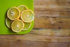 Houten lijst met citroenplakken op een scherpe raad royalty-vrije stock afbeeldingen
