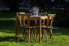 Houten lijst met stoelen in de tuin stock foto