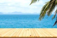 Houten lijst onder kokospalmen met mooie overzees Royalty-vrije Stock Foto's