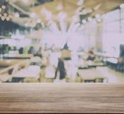 Houten lijstbovenkant met onduidelijk beeld van restaurantbinnenland met partij van bokeh Stock Foto's