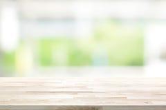 Houten lijstbovenkant op het vensterachtergrond van de onduidelijk beeld witte groene keuken