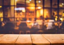 Houten lijstbovenkant op vaag van koffierestaurant met licht goud stock foto
