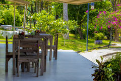Houten lijsten en stoelen in de tuin Stock Fotografie