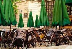 Houten lijsten en stoelen op stadsachtergrond, het concept van de de zomerkoffie met groene paraplu's in openlucht, exemplaarruim royalty-vrije stock foto