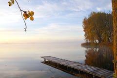 Houten meerbrug en de gouden mist van de de herfstochtend Royalty-vrije Stock Fotografie
