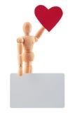Houten mensenstuk speelgoed standbeeld met hart en lege kaart voor tekststudio Stock Fotografie