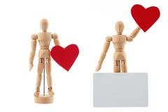 Houten mensenstuk speelgoed standbeeld met hart en lege kaart voor tekststudio Stock Afbeeldingen
