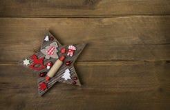 Houten met de hand gemaakte gesneden ster met rode en witte Kerstmis decorat Stock Foto