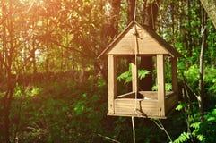 Houten met de hand gemaakte vogelvoeder in vorm van weinig huis Stock Fotografie