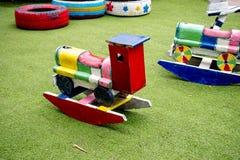 Houten miniatuurauto op de twee lentes op jonge geitjesspeelplaats Stock Foto's