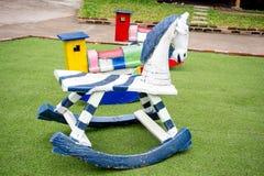 Houten miniatuurauto op de twee lentes op jonge geitjesspeelplaats Royalty-vrije Stock Afbeelding