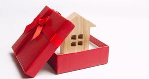 Houten miniatuurhuis in een giftdoos Het huisvesten als gift Win een flat in de loterij Om bezit te erven Vakantiekortingen stock fotografie
