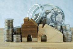 houten miniatuurhuis met stapel muntstukken en muntstukken in glas ja Royalty-vrije Stock Afbeelding