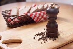 Houten molen voor de peper en een mand brood Stock Afbeelding