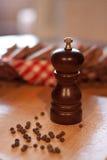 Houten molen voor peper en een mand brood stock foto