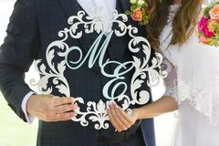 Houten monogram van bruid en bruidegom in witte en lichtblauwe kleuren in handen van bruid en bruidegom royalty-vrije stock afbeelding