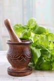 Houten mortier en basilicumbladeren op de lijst Stock Foto