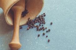 Houten mortier en stamper met zwarte peper op grijze achtergrond Royalty-vrije Stock Foto