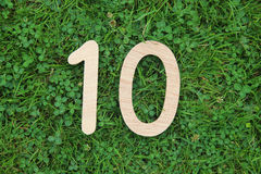 Houten nummer 10 op gras en klaverachtergrond Royalty-vrije Stock Foto