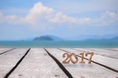 Houten nummer 2017 op plank en tropische strandachtergrond Royalty-vrije Stock Afbeelding