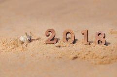 Houten nummer 2018 op strandachtergrond met het idee van de spookkrab Stock Foto's