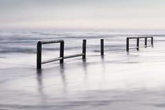 Houten omheiningsinoverzees waterbij zonsondergang Stock Foto's