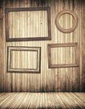 Houten omlijstingen die op bruine plankenmuur hangen Stock Foto's