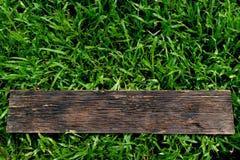 Houten op groen gras voor tekst of reclameconcept stock afbeelding