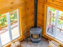 Houten open haard in een houten plattelandshuisje in bos stock afbeelding