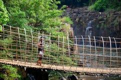 Houten opschorting en bamboebrug voor kruis over stroomrivier stock afbeelding