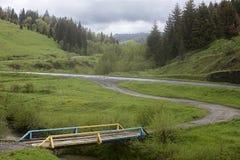 Houten oude brug over een kreek in de vallei van een bergweg Stock Fotografie