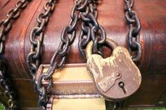 Houten, oude, oude bruine die borst aan een groot die slot wordt gesloten met dikke, sterke metaalkettingen wordt gebonden stock foto
