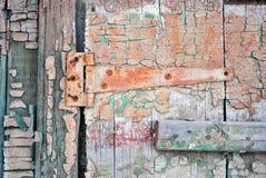 Houten oude deuroppervlakte met roestige die deurscharnier met groene en sepia sjofele verf wordt geschilderd stock afbeeldingen