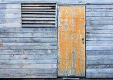 Houten oude door storm geteisterde schuur met een gele oude deur Stock Foto's