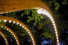 Houten overwelfde galerij met decoratieve verlichting stock foto