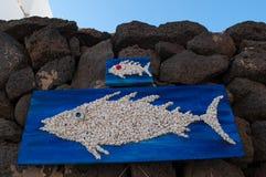 Houten panelen met vissen die op zwarte rotsen hangen Stock Foto